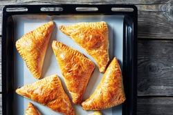 freshly baked puff pastry apple turnover on a silicon mat on a baking tray, horizontal view from above, flatlay, close-up