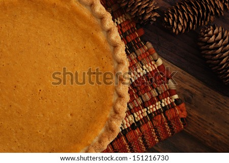 Freshly baked pumpkin pie with placemat and decorative pine cones on rustic wood background. - stock photo