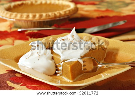 Freshly baked pumpkin pie with whipped cream.  Autumn leaf tablecloth and whole pie in background.  Close-up with shallow dof.