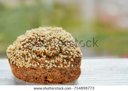 Freshly baked raisins cake with sesame seeds isolated on gray wooden table. Muffin on blurred nature background. Close up view #754898773
