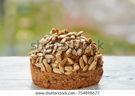 Freshly baked raisins cake with sunflower seeds isolated on gray wooden table. Muffin on blurred nature background. Close up view #754898677