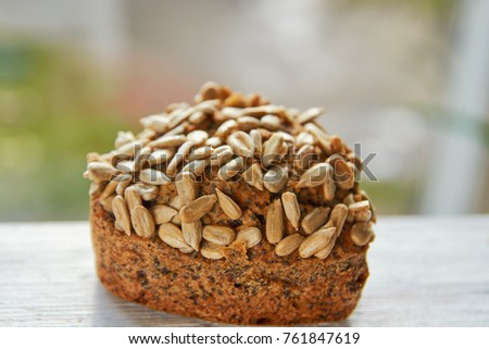 Freshly baked raisins cake with sunflower seeds isolated on white wooden board. Healthy vegetarian muffin on blurred nature background. Close up view #761847619