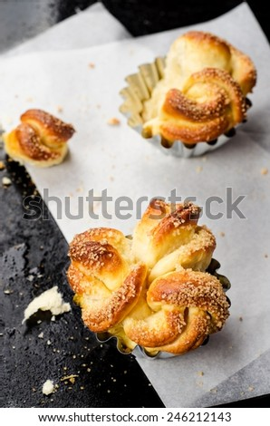 Freshly baked rolls on parchment paper and black iron background