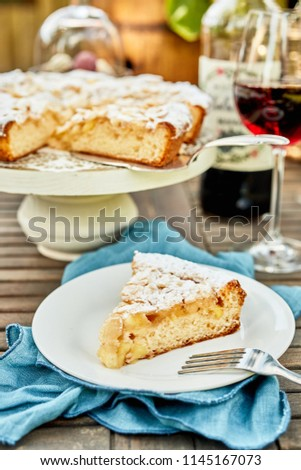 Freshly baked slice of tart on a plate outdoors on a picnic table with glasses of red wine in a close up view