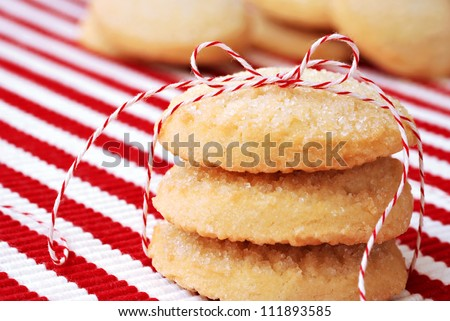 Freshly baked sugar cookies tied with festive baker's twine and stacked on red and white striped placemat.  Macro with extremely shallow dof.