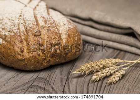 Freshly baked traditional bread on wooden table - stock photo