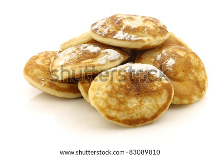 """freshly baked traditional Dutch mini pancakes called """"poffertjes"""" with powdered sugar on a white background"""