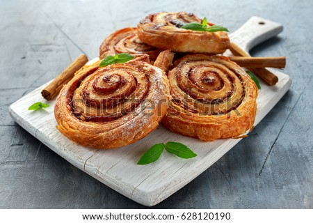 Freshly Baked Traditional Sweet Cinnamon Rolls, Swirl on white wooden board.