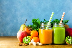 Freshly blended fruit smoothies of various colors and tastes in glass jars in rustic wooden tray. Yellow, green.on wooden table and blue background
