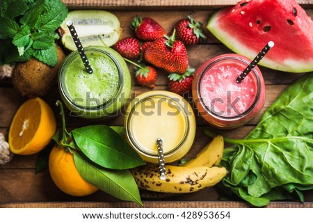 Freshly blended fruit smoothies of various colors and tastes in glass jars in rustic wooden tray. Yellow, red, green. Top view, selective focus #428953654