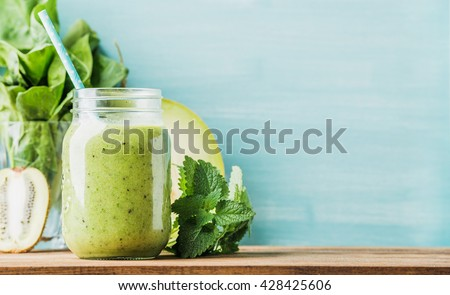Freshly blended green fruit smoothie in glass jar with straw. Turquoise blue background, copy space