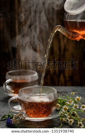 Freshly brewed black tea in a transparent Cup on a transparent saucer on a background of fresh spring flowers! #1351938740
