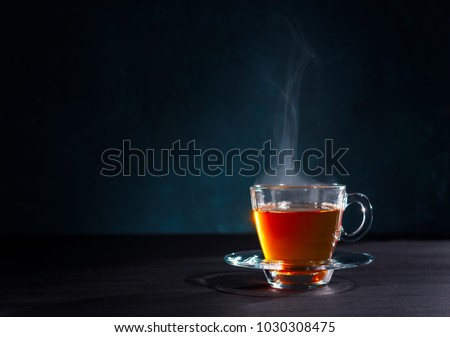 Freshly brewed black tea in a transparent glass Cup,escaping steam,darker background. #1030308475