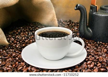 Freshly brewed coffee over dark roasted coffee beans