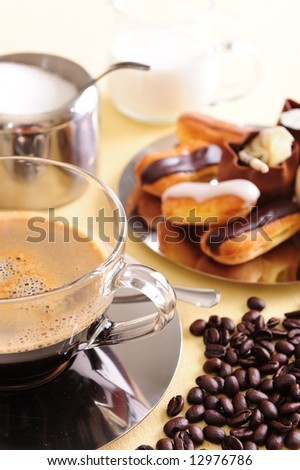 Freshly brewed coffee with a selection of pastries and cakes.  Coffee beans scattered next to the cup for extra effect.