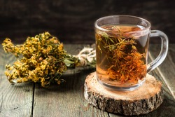 Freshly brewed tea with useful dried St. John's wort in a glass mug on a wooden table. Selective focus