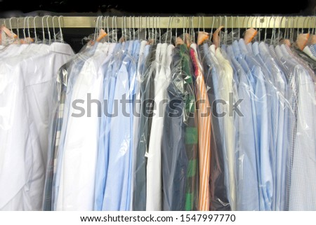 Freshly cleaned men's shirts and ladies blouses in a dry cleaning, hung on hangers and protected by plastic film. Ready for pick up