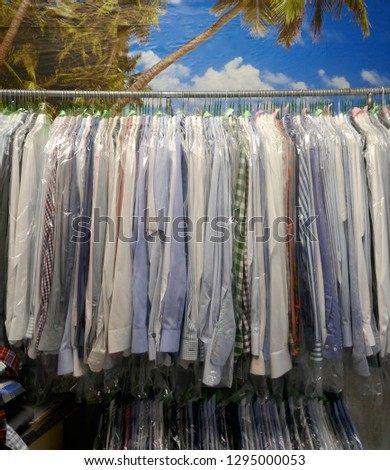 Freshly cleaned men's shirts and ladies blouses in a textile cleaning, hanging on hangers and packed in plastic wrap