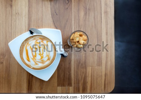 Freshly coffee macchiato with caramel sauce on top next to a glass of salted crackers or biscuit abc shape, top view. Caramel Macchiato coffee.