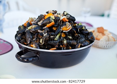 Freshly cooked bouchot mussels in metal pot on table