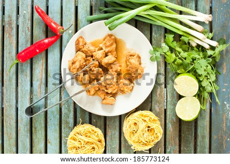Freshly cooked chicken pieces on a small plate with raw ingredients and dried noodles