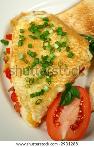 Freshly cooked omelette with toast and tomato.