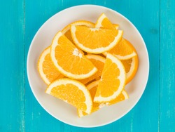 Freshly Cut Natural Healthy Juicy Organic Orange Slices Or Segments On A Plate, Against A Blue Wooden Table, Flat Lay Composition With No People,