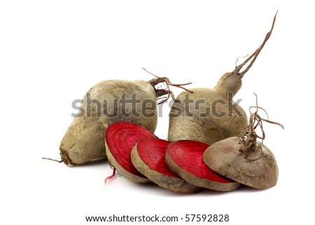 freshly cut slices of beetroots and two whole ones on a white background