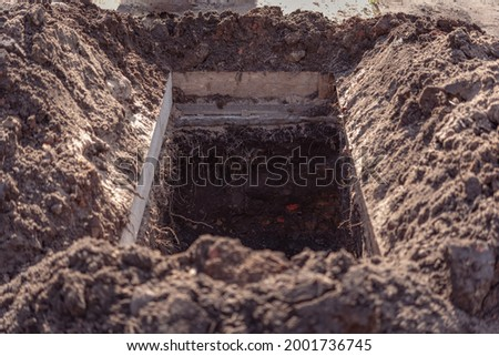 Freshly dug grave pit at cemetery, a close-up. Stock fotó ©