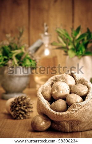 Freshly dug potatoes in burlap sack in rustic setting with herbs in background