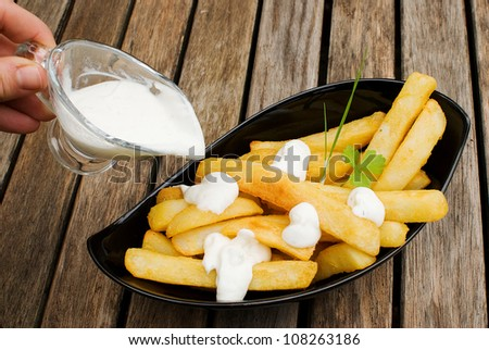 freshly fried potatoes in black plate over wooden old table