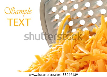 Freshly grated cheddar cheese with stainless steel grater on white background.  Macro with shallow dof.
