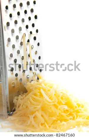 Freshly grated cheese and greater isolated on white