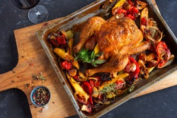 Freshly grilled roast chicken. Mediterranean preparation with vegetables and herbs on rustic wooden cutting board. Food photography lay flat with space for text. Top view.