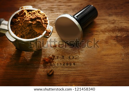 Freshly ground coffee beans in a metal filter on a wooden background with copyspace during preparation of a cup of aromatic filter coffee or espresso