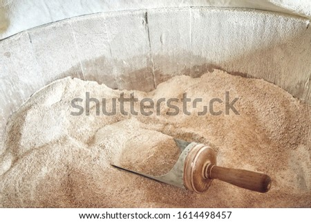 Freshly grounded Organic Wheat Bread Flour into a wooden bucket with a shovel.