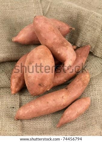 Freshly grown sweet potatos isolated on hessian