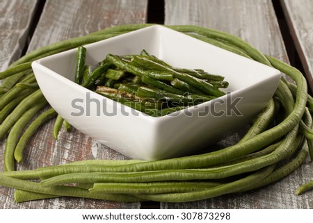 Freshly harvested Asian green beans on a weathered barn wood table with a white bowl of stir-fried beans
