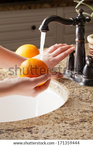 Freshly harvested California Oranges with running water at a sink; hands turning off faucet