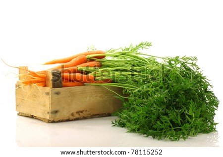 freshly harvested carrots in a wooden crate on a white background