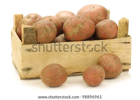 "freshly harvested dutch potatoes called ""Bildtstar"" in a wooden crate on a white background"