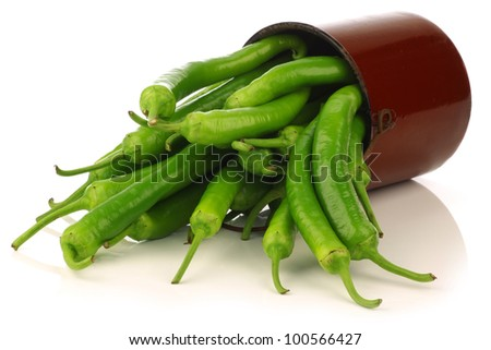 Freshly harvested jalapeno peppers in an enamel cooking pot on a white background