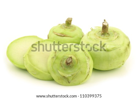 freshly harvested kohlrabi cabbages and a cut one on a white background