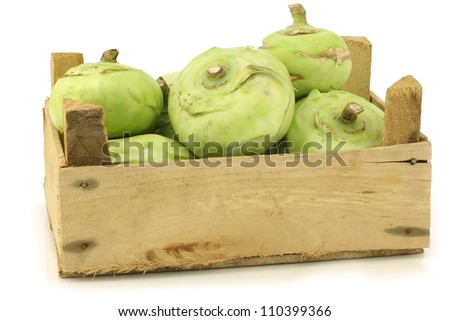 freshly harvested kohlrabi in a wooden crate on a white background - stock photo