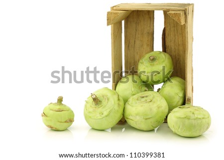 freshly harvested kohlrabi in a wooden crate on a white background
