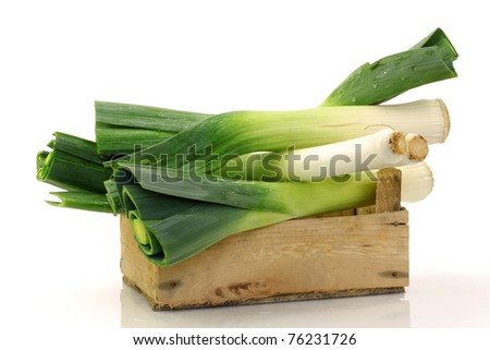 freshly  harvested leek in a wooden box on a white background