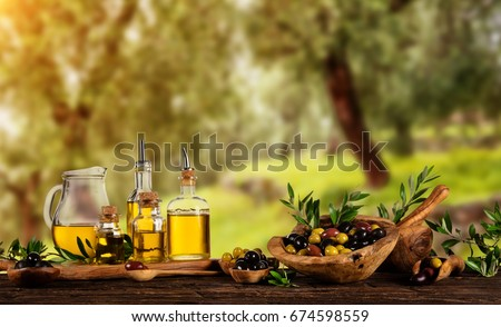 Freshly harvested olives berries in wood bowls and pressed oil in glass bottles. Still life of food preparation served on old wooden planks. Free space for text