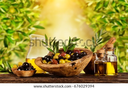 Freshly harvested olives berries in wood bowls and pressed oil in glass bottles. Still life of food preparation served on old wooden planks. Free space for text. Very high resolution of image