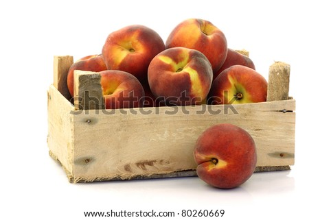 freshly harvested peaches in a wooden crate on a white background