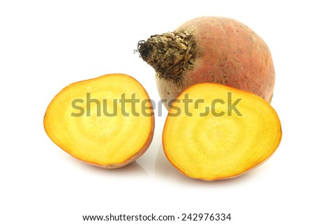 freshly harvested yellow beet and two halves on a white background
